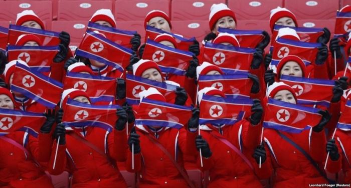 Болельщицы держат флаги КНДР на соревнованиях по горнолыжному спорту.