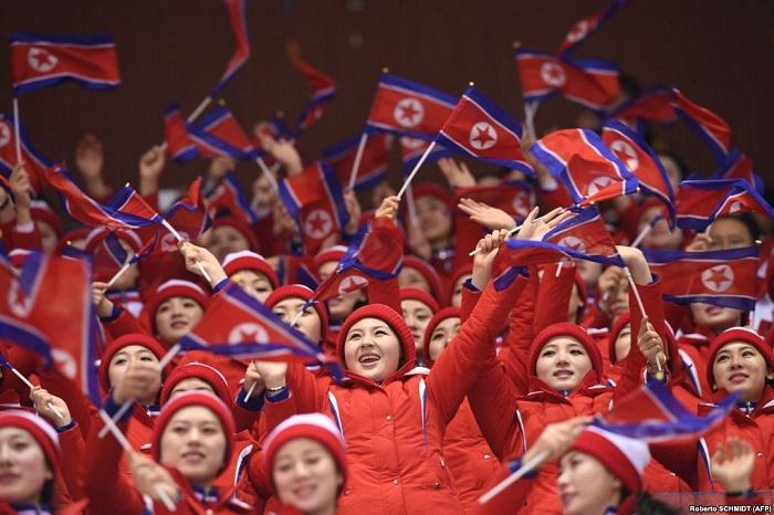 Северокорейские болельщицы размахивают флагами КНДР во время соревнований.