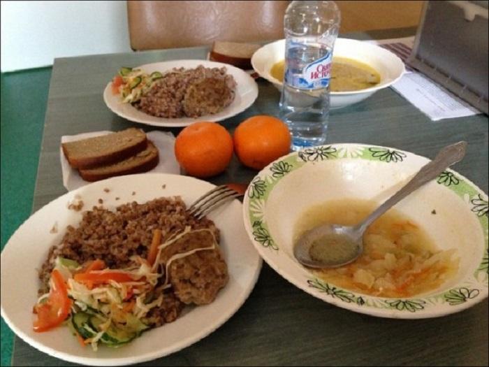 Суп, котлета с гарниром из гречки, овощной салат, хлеб и мандарины.