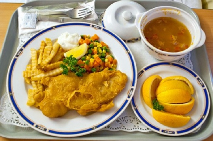 Рыба и картофель фри, овощи и суп.
