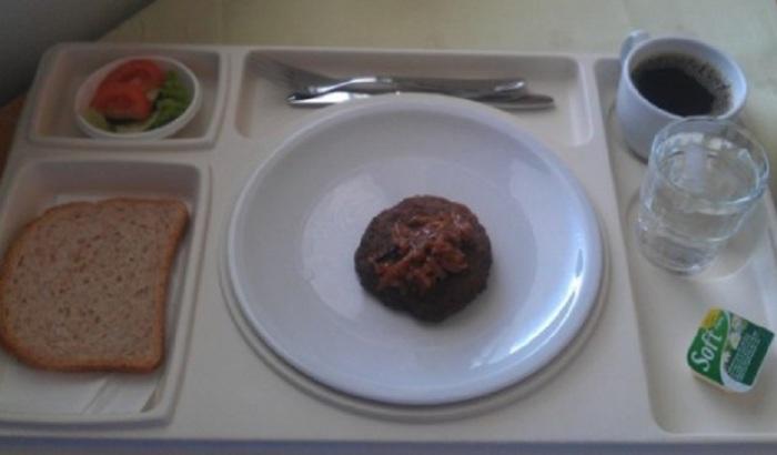 Хлеб, салат, соус и большая котлета из натурального мяса с тушеной капустой.