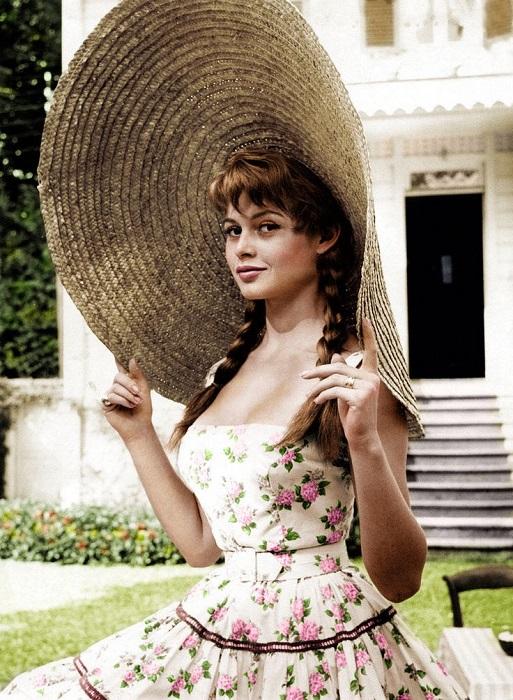 Раскрашенный портрет популярной французской актрисы Брижит Бардо в соломенном сомбреро и сарафане с цветочным принтом.