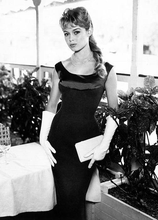 Очаровательная Брижит Бардо в черном платье-футляре, дополненном с белым клатчем и классическим жемчужным ожерельем.