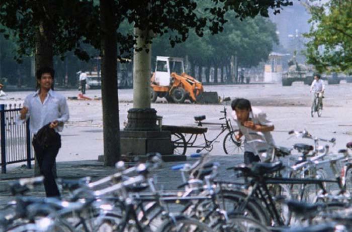 Трое неизвестных спасаются бегством, в то время как человек на заднем плане пытается загородить дорогу приближающимся танкам. 4 июня 1989 года.