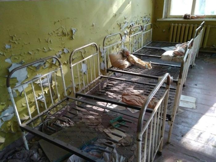 Множество игрушек и личных вещей, брошенных в здании бывшего детского сада.
