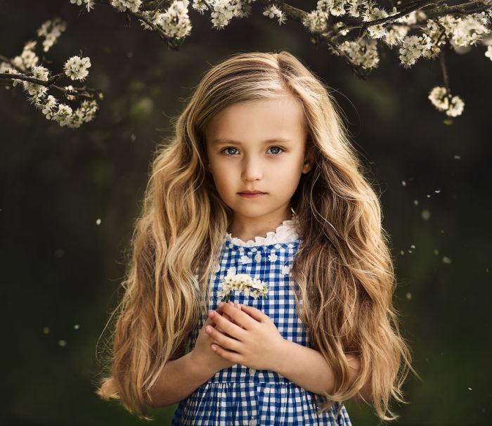 Малышка с восхитительными волосами под вишневым деревом.