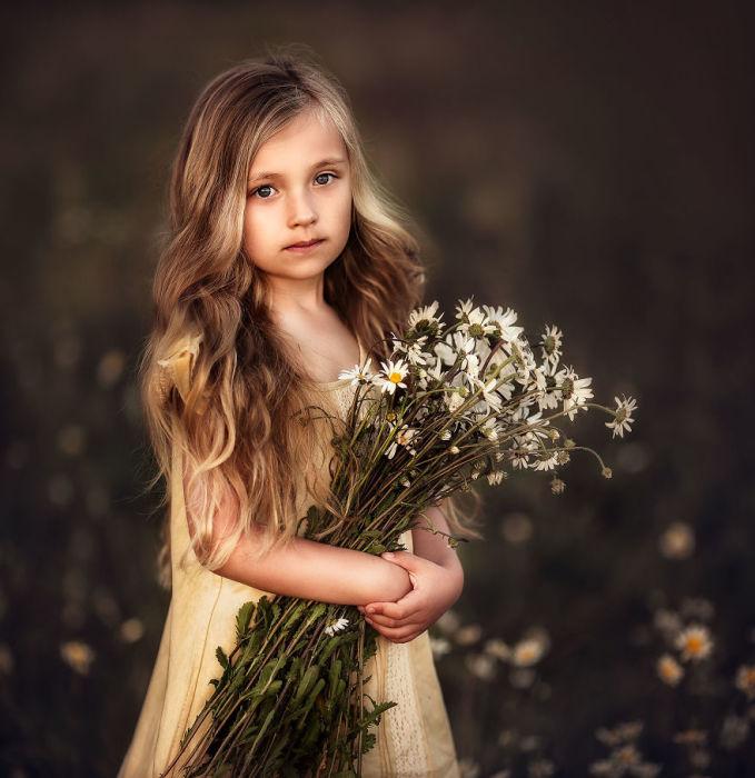 Так и хочется вдохнуть неповторимый аромат полевых ромашек, которые держит маленькая красавица.