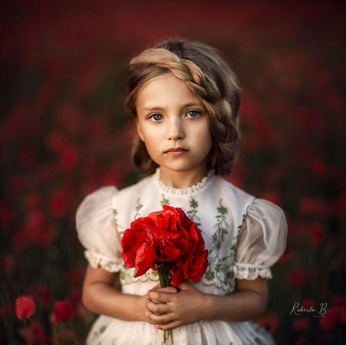 Красивый портрет маленькой девочки с букетом ярко – красных маков.