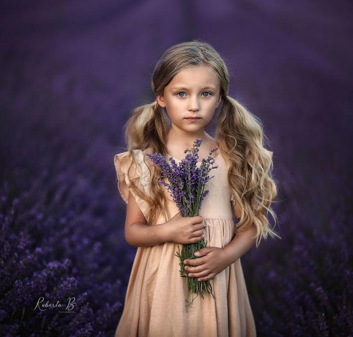 Маленькая фотомодель с букетом из ароматных и нежных цветков лаванды.