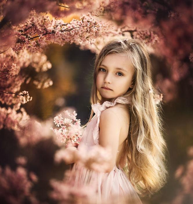 Чудная малышка позирует для мамы в прекрасном вишневом саду.