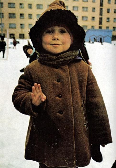 Детишки на заснеженной площадке стоят одинаковые, как пингвины.