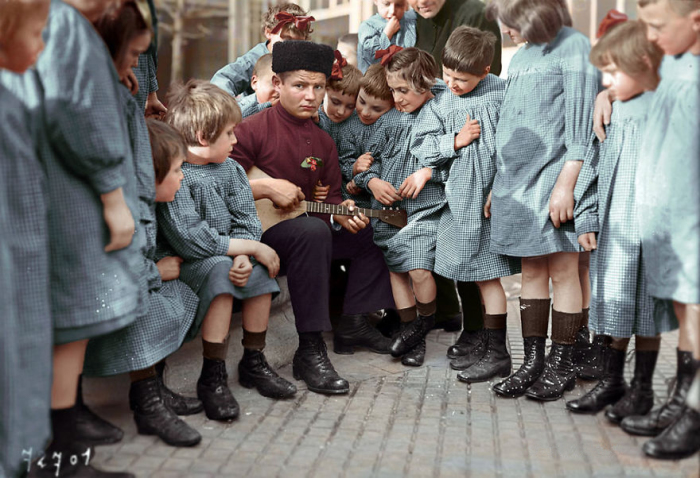 Мальчик в народной одежде с группой детей.
