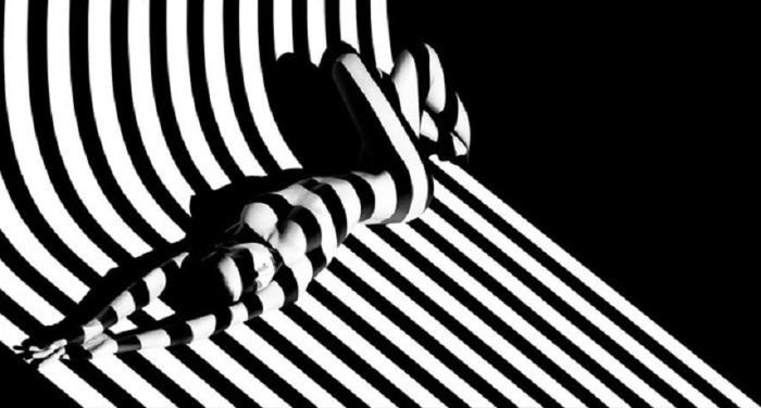 Гламур-модель в полуобнаженном виде с тенями полосками на теле.