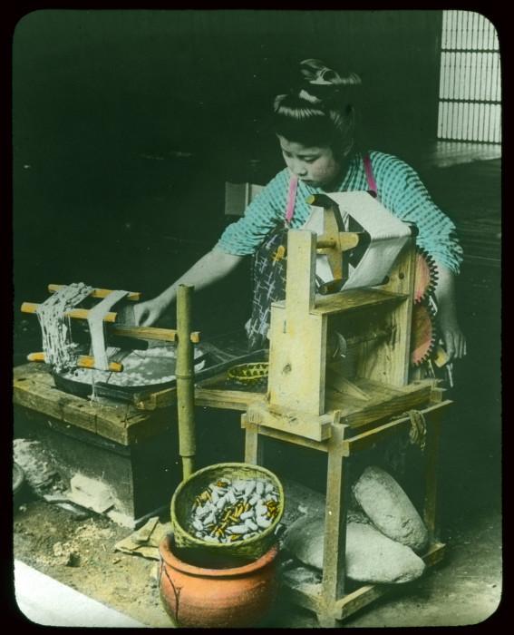 Женщина работает на специальном станке для извлечения шелковой нити.
