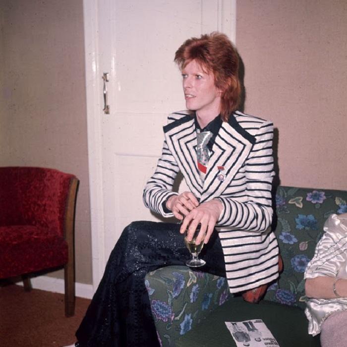 Дэвид Боуи в полосатом пиджаке с широкими лацканами и брюках-клеш с узором в виде блестящих квадратов.