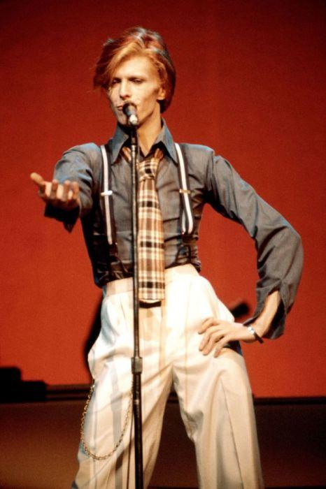 Британский певец выступает в Radio City Music Hall в сценическом костюме с подтяжками и галстуком в клетку.