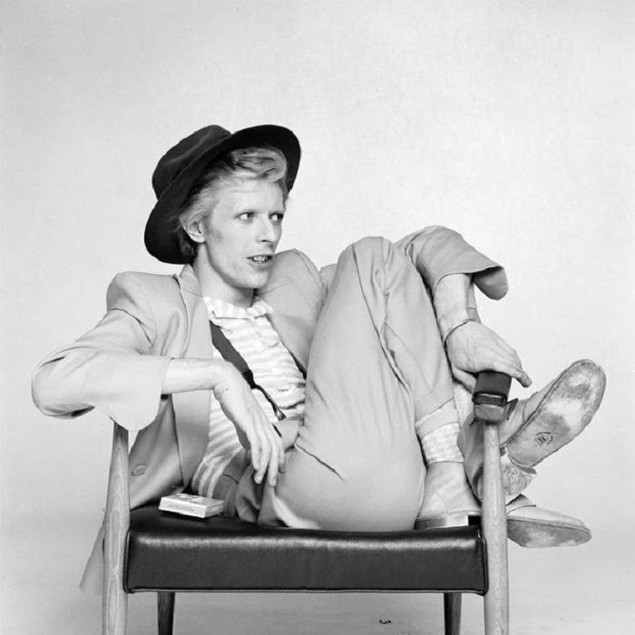 Монохромная промо-фотография знаменитого британского исполнителя в классическом костюме и шляпе.