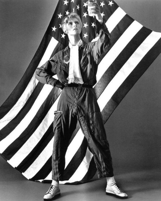 Монохромный портретный снимок британского рок-музыканта и певца в комбинезоне пилота на фоне американского флага.