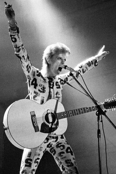 Британский рок-певец в комбинезоне с принтом во время живого выступления в рамках первого этапа турне «Ziggy Stardust Tour».