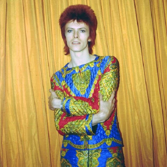 Легендарный певец в ярком стеганом костюме, созданном для тура «Ziggy Stardust» позирует в гостиничном номере в Нью-Йорке.