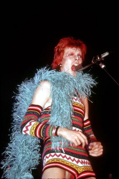 Дэвид Боуи во время выступления на своем шоу в Лос-Анджелесе – вязаный комбинезон с геометрическим орнаментом и боа из голубых перьев.