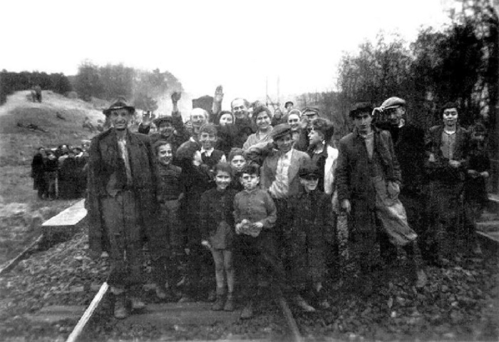 Фотография запечатлела группу выживших изнеможенных людей с радостью на лице.