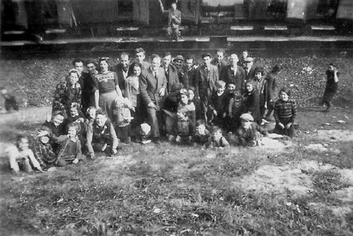 Узники сделали фотографию на фоне стоящего позади поезда смерти.