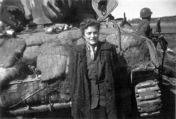 Женщина на имя Джина Раппапорт из поезда стоит возле танка и танкистов.