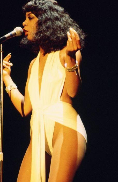 Смелый сценический костюм Донны Саммер – белое откровенное платье-купальник и золотые аксессуары.
