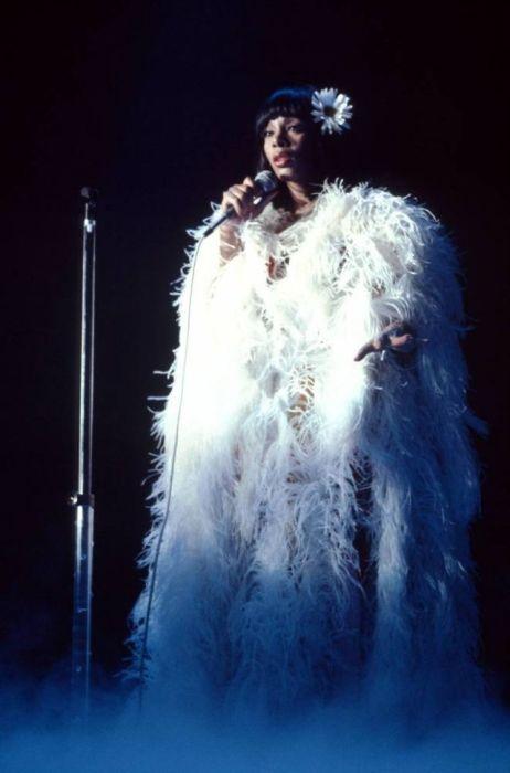 Американская певица Донна Саммер исполняет песню на концерте в плаще из белых перьев в 1979-м году.