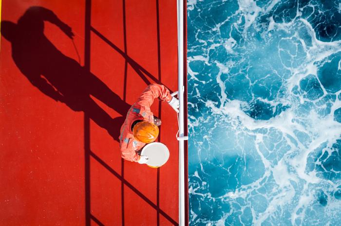 Голубые волны океана бьются об борт грузового судна. Автор фотографии: Зай Яр Лин (Zay Yar Lin).