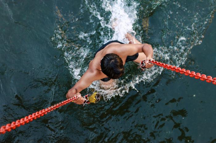 Мужчина, который поднимается по цепям из воды. Автор фотографии: Чудхари (Harsh Choudhary ).