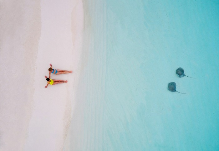 Девушки изображающие скатов на песке. Автор фотографии: tahitiflyshoot.