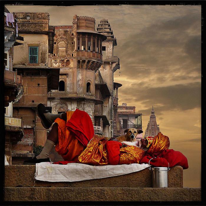Аскет-садху, спящий на заходе солнца на фоне города Варанаси.