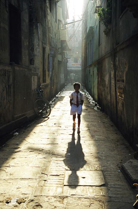 Учащийся школы возвращается домой после уроков по узким улочкам города.