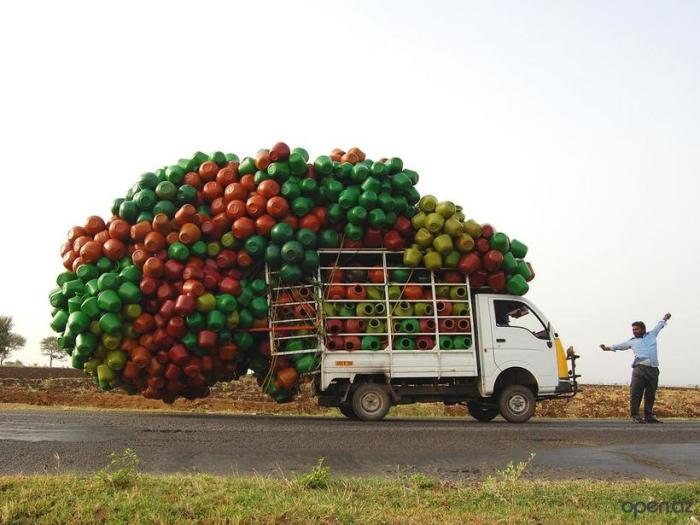 Маленький индийский грузовик с кузовом, переполненным пластиковыми кувшинами.