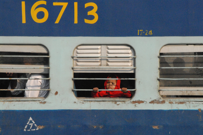 Маленькая путешественница терпеливо ожидает отправления поезда со станции.