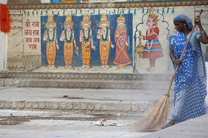 Женщина в голубом сари, наводящая чистоту на одной из улиц города Варанаси.
