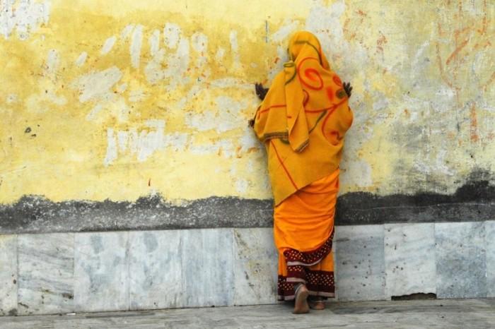 Молящаяся женщина возле стены храма в Орчхе во время духовного праздника.