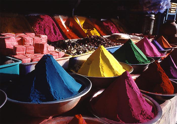 Яркие и разноцветные сухие краски на прилавке магазина в Индии.