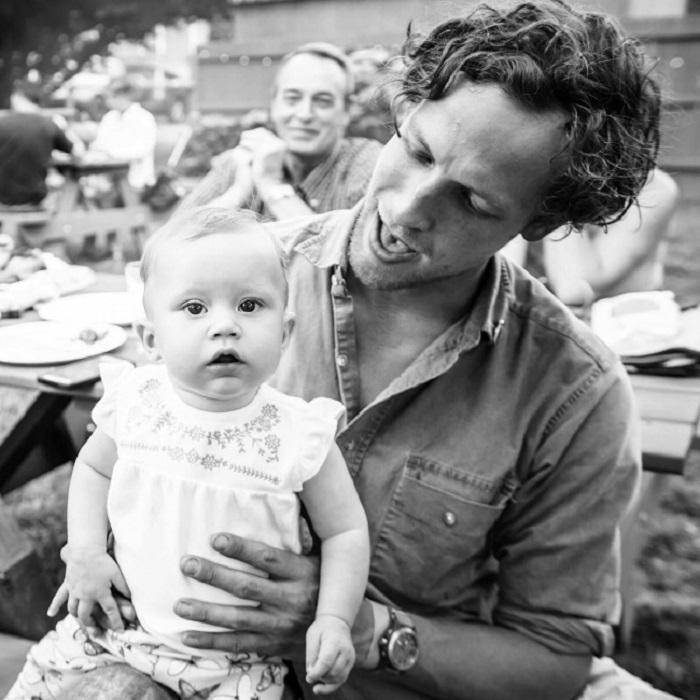Отец наблюдает за сыном, который проводит время со своим ребенком.