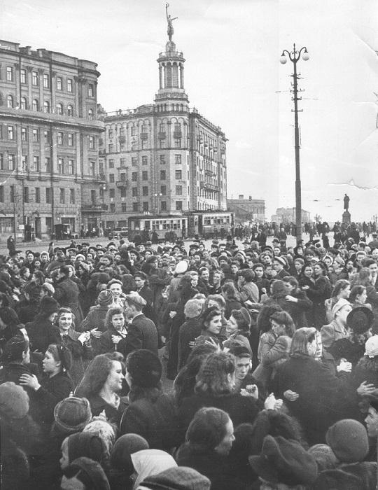 Большое количество женских пар танцующих на площади.