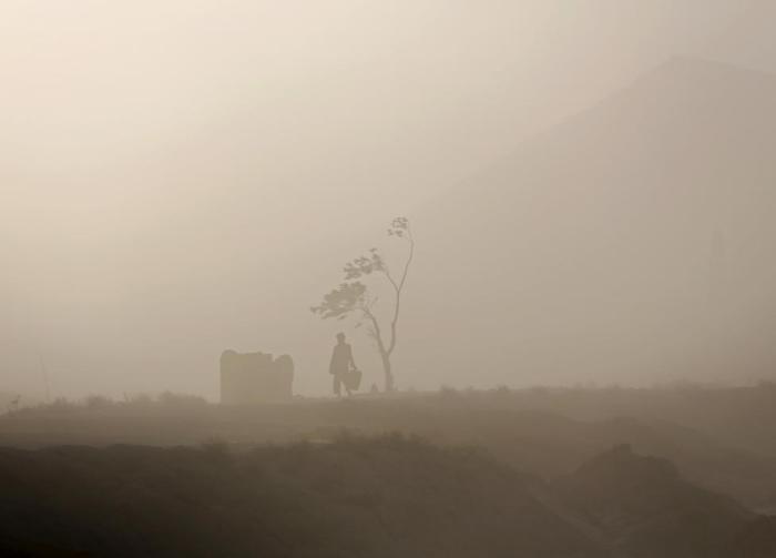 Человек идет сквозь песчаную бурю, которая несёт клубы пыли, песка и грязи.