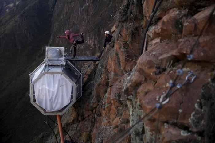 Туристы поднявшиеся с помощью железного троса на вершину скалы, чтобы провести ночь в прозрачной палатке.