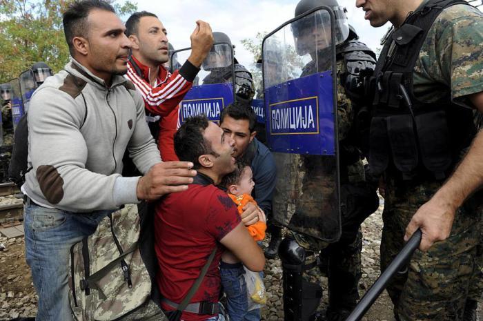 Мигрант с ребенком пытается пройти через полицейский заслон во время столкновений мигрантов с правоохранителями на греко-македонской границе.