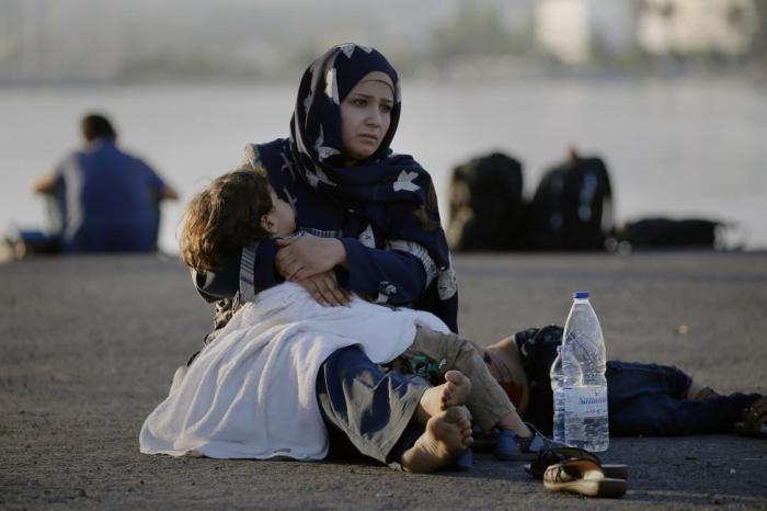 Сирийская беженка с ребенком на руках в порту греческого острова Кос ждет регистрации, после которой станет возможным дальнейшее путешествие на пароме в Европу.