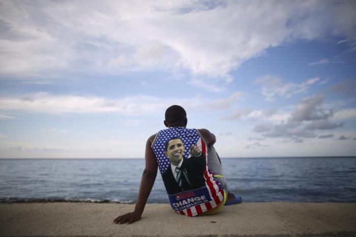 Студент медицинского факультета мечтает об Америке на берегу океана, одет в футболку с изображением президента США Бараком Обамой.