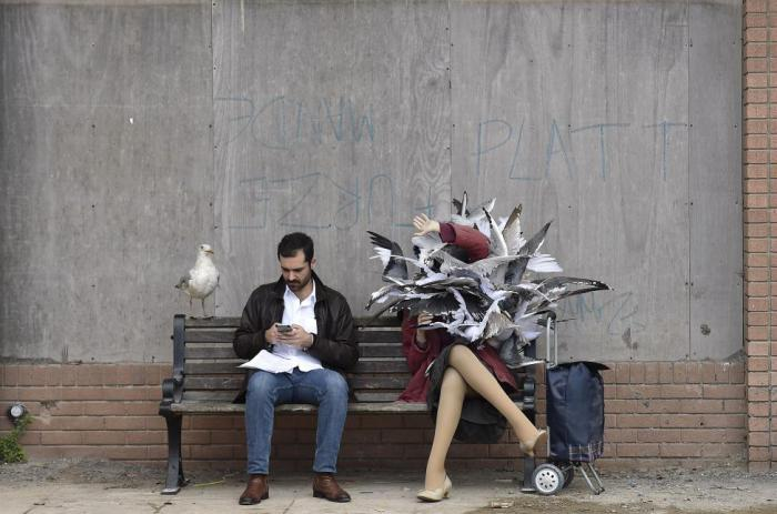 Мужчина сидит на скамейке рядом с одной из скульптур в тематическом парке в стиле арт-инсталляции британского художника Бэнкси.