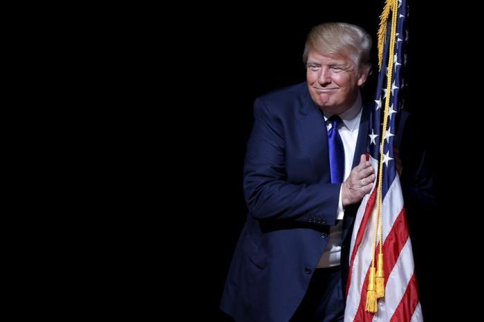 Республиканский кандидат в президенты обнимает американский флаг, выходя на сцену во время встречи с избирателями.