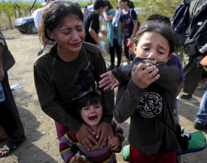 Девочки плачут из-за того, что их разлучили с семьей на границе Македонии и Греции.